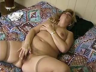Plump blonde caresses her wet pussy